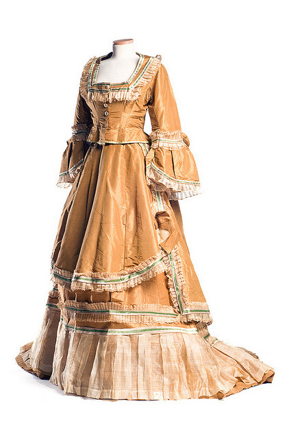 tawnyscostumesandcuriosities:    Saffron gold silk dress, c. 1869, with organdy and lace edging, green and cream satin ribbons. The overskirt gathers up in to add emphasis to the back, a precursor to the bustle. This gown was worn by Frances Olmsted (later Mrs. Richard Maynard Marshall) when she attended the first St. Cecilia Ball held after the Civil War.