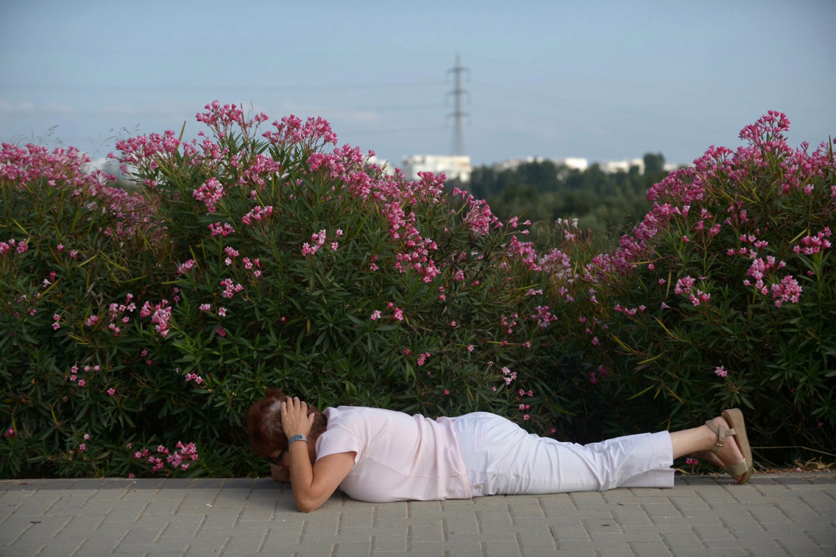 Avi Roccah | An Israeli woman covers her head and lays on the ground while sirens sound in the southern city of Ashdod, Israel‬.