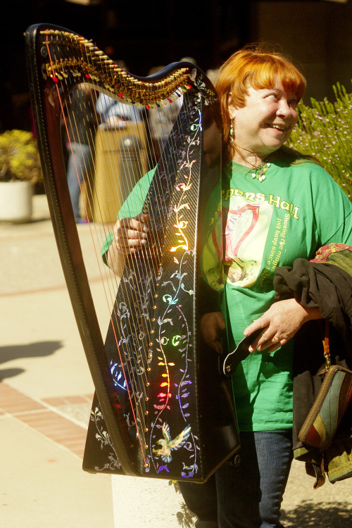 "Harp flash mob! On this past day of St. Pat, green-wearing, harp-playing musicians suddenly swarmed audience members heading for a show by the California Pops Orchestra at Smithwick Theatre. There's no better hors d'oeuvre for a Big Band show than a surprise helping of ""Danny Boy"" and other Irish tunes. We hear there was impromptu jigging. Word is the mobbers came from the Harpers Hall & Culinary Society. Pops conductor Kim Venaas, always ready for anything, cracked a few Irish jokes and the afternoon was off and running. Pictured: Deb Knodel of San Mateo with a black carbon-fiber Irish harp. Photogs on the scene were Sam Huie & Jeoff Sheau."
