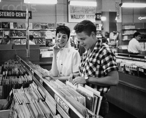 kbtumbls:  theniftyfifties:  Eddie Cochran goes record shopping.  …with his fiance (and genius song writer), Sharon Sheeley.
