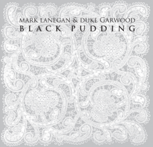 "Mark Lanegan & Duke Garwood - Black Pudding [Ipecac; 2013] The voice of Mark Lanegan has painted a demur portrait; a gothic world clouded by smoke and heavy with forbidden sensuality. Throughout the days of grunge with oft-ignored foursome Screaming Tree through a bevy of solo and collaborative releases, that ebon-drenched larynx has belched forth a graveled croon that is as dark as it is uplifting. We are given a glimpse into history as it happened, not as the victors have scribbled. It's this ability to tap into the primal–the sense to understand humanity at its most vulnerable–that attracts many to Lanegan's point-of-view. His visceral descriptions of the physical world leave their mark, but rarely has the melody been more than a secondary emotion to the wrought-iron expositions of the master lyricist. Despite tempered pairings with Greg Dulli, Josh Homme and Isobel Campbell, it's taken multi-instrumentalist Duke Garwood (a relative unknown to anyone who ignores inserts and booklets) to match the timbre of Lanegan's soul in song. Black Pudding is thick with the bonds of brotherhood. Garwood's darkness melds with Lanegan's mysticism, the pall of forlorn guitars and spectral drones drenching the pair's first outing in viscous tribulation. But anyone adept at tapping into the human psyche is equally skilled at capturing the hopefulness of despair; the noble pursuit of the silver lining, no matter how obscured. ""Cold Molly"" is the eye of the storm, a funk-soul-blues dirge disguised as an up-tempo blessing. Much like Dulli tried to conjure with Lanegan in The Gutter Twins, Garwood makes good with a fractured melody as hot New Orleans summer and as cool as a Mississippi delta strut. The western themed ""Death Ride"" is typical Lanegan imagery, but Garwood's background din signals the danger approaching. It's reminiscent of Screaming Trees' ""Gospel Plow,"" but far more realistic in its depiction of death than Lanegan's elder tune. It's a trick played throughout the album at just the right moments. When the robotic tempo of ""Mescalito"" threatens to crumble the album's first half, the ghostly buzz of ""Sphinx"" recaptures the mood. And though ""Cold Molly"" doesn't disturb the story, it does disrupt the ride. But the ethereal ""Shade of the Sun"" reins both back. The funny thing about history is how often society forgets its implications. Much of the same can be said about Lanegan. Few speak of Screaming Trees in the same company of lesser but highly recognized alterna-acts. A string of deeply personal solo albums are glossed over for his prettier collaborations. Yet Black Pudding is distinctly Lanegan, even as it is accurately Garwood. These two are kin, bonded by context and possessed by valiance. With these men, the past rests in the hands of capable storytellers speaking in allegory and truth. But above all else, Black Pudding is an album of modern times. Doomsayers are well aware of the cliché, Lanegan and Garwood hell bent on not repeating the same mistakes."
