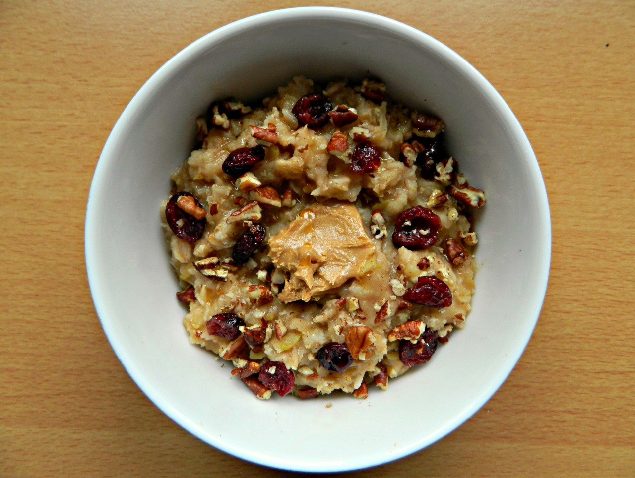Apple and cinnamon oatmeal with crushed pecans, dried cranberries, natural peanut butter and a drizzle of maple syrup. (Oatmeal - 1/3 cup oats, 2/3 cup almond milk, 2/3 cup water, 1 tsp cinnamon, 1 small grated apple, dash of vanilla.)