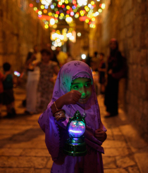 awkwardsituationist:  a palestinian girl celebrating ramadan festivities in an alley of jerusalem's old city. aug. 10 2010. photo muhammed muheisen