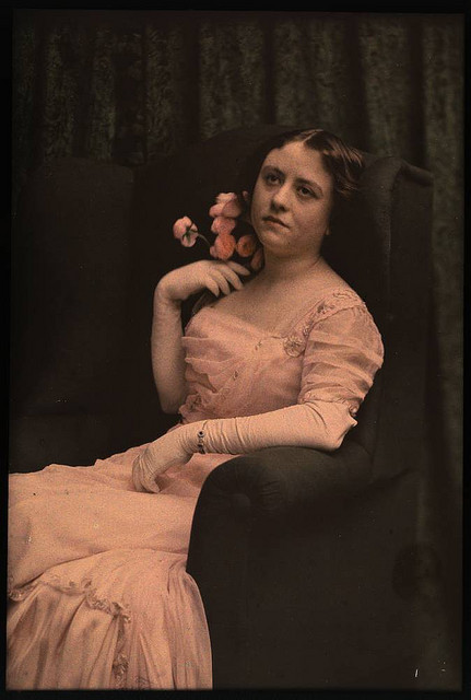 Woman in pink dress sitting in chair holding roses by George Eastman House on Flickr.