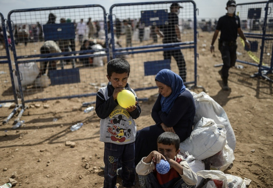 Syrian Kurdish children blow up balloons as they cross the border between Syria and Turkeyat the southeastern town of Suruc in Sanliurfa province on September 27, 2014. (Bulent Kilic/AFP/Getty Images)