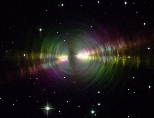 "Rainbow Egg Nebula  Resembling a rippling pool illuminated by underwater lights, the Egg Nebula offers astronomers a special look at the normally invisible dust shells swaddling an aging star. These dust layers, extending over one-tenth of a light-year from the star, have an onionskin structure that forms concentric rings around the star. A thicker dust belt, running almost vertically through the image, blocks off light from the central star. Twin beams of light radiate from the hidden star and illuminate the pitch-black dust, like a shining flashlight in a smoky room. The artificial ""Easter-Egg"" colors in this image are used to dissect how the light reflects off the smoke-sized dust particles and then heads toward Earth. Dust in our atmosphere reflects sunlight such that only light waves vibrating in a certain orientation get reflected toward us. This is also true for reflections off water or roadways. Polarizing sunglasses take advantage of this effect to block out all reflections, except those that align to the polarizing filter material. It's a bit like sliding a sheet of paper under a door. The paper must be parallel to the floor to pass under the door… (read more: Wired Science) Image: NASA and The Hubble Heritage Team (STScI/AURA) [high-resolution] Caption: Hubble Heritage Team"
