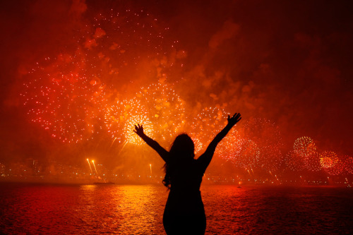Pilar Oliviares/Reuters A woman celebrates the new year as she watches fireworks exploding above Copacabana beach in Rio de Jeneiro on Jan 1. More than two million people gathered along Rio's most famous beach to witness the 20-minute display and celebrate the beginning of a new year.