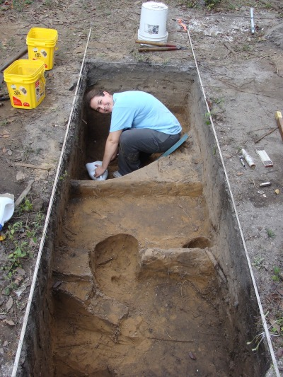 fpannortheast:  Sarah excavates a British Period well at 74 Spanish Street.  In the foreground are remnants of a 19th-century post hole (center), a 19th-century trash deposit (front right), and an early 18th-century trash deposit (front left).  Photo courtesy of the City of St. Augustine's Archaeology Division.