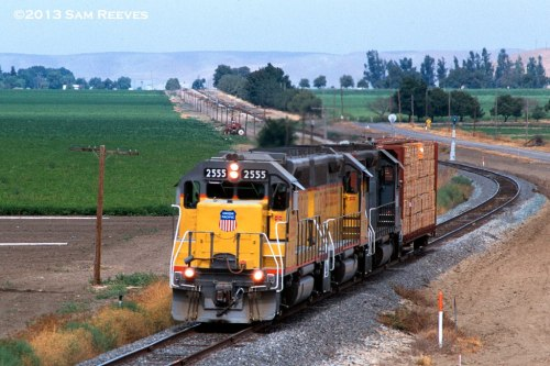 "Another old slide from 2000. The Union Pacific ""Santa Magarita Turn"" takes a single centerbeam car of lumber down the Coast LIne. They have just passed San Ardo, and will have about another 45 minutes before they reach their destination of Paso Robles. I think all three engines should be enough on this day!"