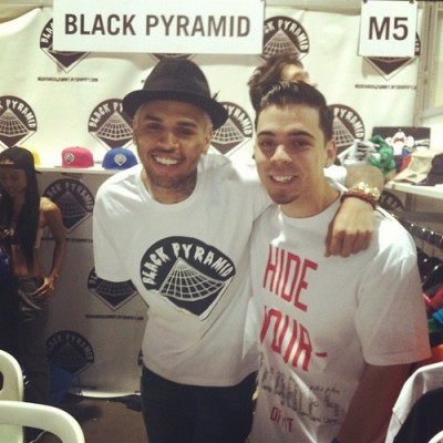 On Saturday…Chris Brown posing for pics at The Agenda Trade Show to promote his new clothing line, Black Pyramid . Yes, that's his ex, Karrueche in the background…