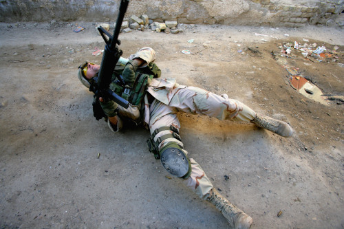 BAGHDAD, IRAQ - FEBRUARY 2005:  First Sgt. Troy Hawkins falls wounded to the ground during a firefight in the troubled Haifa Street area February 16, 2005 in Baghdad, Iraq. Sgt. Hawkins was wounded in the leg and shoulder but continued to direct troop movement before walking out of the fire zone. (Photo by Brent Stirton/Reportage by Getty Images)