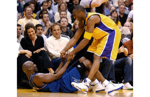 "Kobe Bryant helping Michael Jordan up off the court in a game against the Wizards. Ironically, Kobe is wearing the Air Jordan 8 ""Lakers/Kobe"" PE."