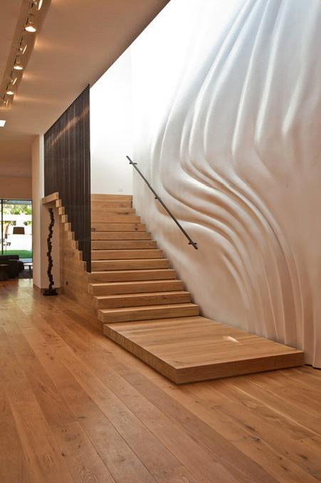 designed-for-life:  Now here is a unique decorating idea for stairway walls. The sole purpose of a stairway is to get you from one floor to the other. People don't gather in staircases in homes to socialize and hang out. But still we look for ways to create interest in a stairway by hanging picture frames, using wallpaper or incorporating decorative lighting to create a nice atmosphere while the space is in use. Or as in this example, you could add a custom-molded wall for a very striking effect. The contrast of the smooth undulated white wall and the straight lines of the wooden stairs is very pleasing to the eye. This idea is highly unusual but provides a prominent contemporary look to the space. Very inspiring and very creative – you could even say it's quite artistic. Learn more about the architects at Assemblage+. http://www.trendir.com/interiors/decorating-ideas-for-stairway-walls.html