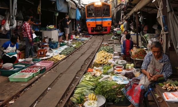 Yes that's an oncoming train: Thai vendors selling their goods on a railway track at Talad Rom Hoop, meaning 'closing umbrella market' in Mae Klong district, Samut Songkhram province, Thailand. Trains pass 8 times each day. Photograph: Rungroj Yongrit/EPA (via guardian:)