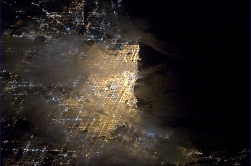 colchrishadfield:  Chicago, a bright spot on the tip of Lake Michigan, glowing through the clouds.