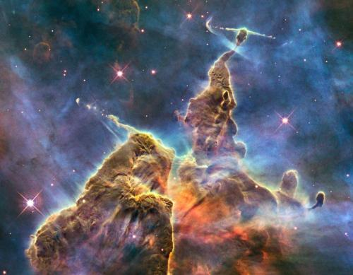 Plumes Within the Carina Nebula  The Carina Nebula (also known as the Great Nebula in Carina, the Eta Carina Nebula, or NGC 3372) is a large bright nebula that surrounds several open clusters of stars. Eta Carinae and HD 93129A, two of the most massive and luminous stars in our Milky Way galaxy, are among them. The nebula lies at an estimated distance between 6,500 and 10,000 light years from Earth. It appears in the constellation of Carina, and is located in the Carina–Sagittarius Arm. The nebula contains multiple O-type stars… (read more: Wikipedia)                           (photo: NASA)