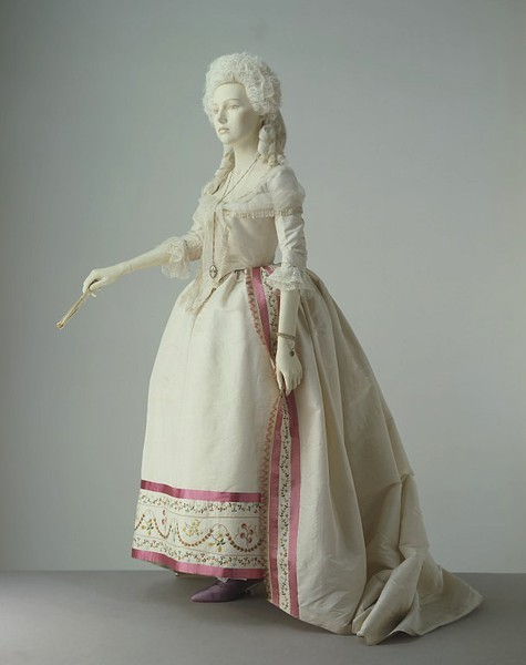 Robe, 1780-85 France, the Victoria & Albert Museum  This gown demonstrates the fashionable styles in women's formal dress of the 1780s. The hoop has changed from the square shape of earlier decades to a round profile. A stomacher is no longer needed, because the gown now meets in the front. The cream silk is adorned only at the edges with an embroidered band, ribbon and a stencilled fringe. This restraint in decoration illustrates the growing influence of the Neo-classical style in textile design.