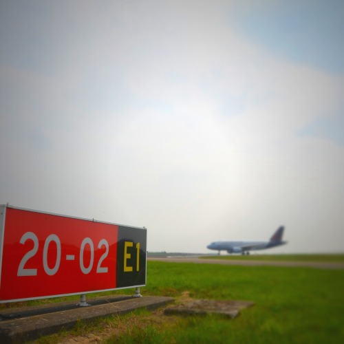 Runway 02/20 gets a new name: 01/19 Due to the shift of the magnetic north a project has recently been started to change the name of runway 02/20 to 01/19. This may almost sound like an April fool's joke, but it certainly isn't. There's a simple explanation for it. All over the world runways bear a number from 01 to 36, depending on their direction with respect to the compass: the number 09 stands for the east (90°), 18 for the south (180°), 27 for the west (270°) and  36 for the north (360°). As runways can be used in two directions, which are 180° apart, they have two numbers that indicate both, with a difference that is always 18. That's why runway 02 is also runway 20 in the opposite direction, and runway 07 is also runway 25. (*)  Years ago, when this denomination began to be used, a small detail was overlooked. The compass aligns itself with the magnetic north, the location of which is not completely stable. The magnetic north of our planet shifts a bit each year, so that at a certain moment 11 degrees becomes 10 degrees, and a few years later even 9 degrees. So eventually some airports find themselves with a runway whose name no longer matches the reality of the compass.We've seen these storm clouds gathering for a few years already, but there's no getting away from it now: our runway 02/20 needs to renamed 01/19 in September 2013. Although this is not the first time a runway needs to be renamed for the same reason at a large airport, it is rather rare and such changes are not much documented. The two parallel runways at Brussels Airport adopted new names in the early 1970s. They used to be 08L/26R and 08R/26L. And now it already looks like they will need to be changed to 06/24 in a few years' time.  Putting a runway name change into force requires more than just painting the new number on both sides of the runway. The fact is that the name of a runway appears in hundreds if not thousands of official documents and on plans, and they all have to be updated. Since any misunderstanding about the number of the runway could have serious operational consequences, this kind of name change must be carried out safely and flawlessly, in close consultation with all parties concerned. A project team maps out all the possible ramifications of the change.  A dedicated project team is making a complete and thorough assessment of the impact of the name change on operations at the airport. It is listing the effects on the activities of the respective companies and departments at Brussels Airport. At the moment there are few documented cases that can serve as references. Our experiences with the name change will therefore be thoroughly documented so that they can be useful in the event of subsequent name changes.  During the night of 18 to 19 September the name will be changed in all the databases used for aeronautical navigation all over the world. At the same time all the signs at the airport will be changed too, and the lettering on the runway itself will be repainted.To avoid any misunderstanding: tomorrow's 01/19 will be the exact same runway as today's 02/20: it will only wear a new number painted at both ends.    (*) Bonus: To avoid confusion, parallel runways also get a letter in their name: L (Left) or R (Right). That's why we have 07L/25R and 07R/25L at Brussels Airport. At airports with three parallel runways the middle one gets the letter C (Centre). Even bigger airports, with four or five parallel runways, like Atlanta, Chicago, Dallas, Denver, Detroit, Los Angeles, Orlando, etc., avoid misunderstandings – and therefore accidents – by adding ten compass degrees to their names each time. Atlanta, for example, has 26L, 26R, 27L, 27R and 28, although the five runways all point in exactly the same direction.