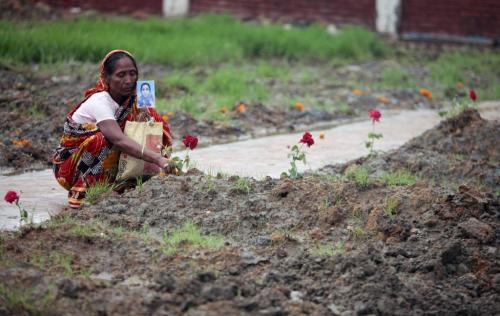 fotojournalismus:  A woman sits beside an unnamed grave holding a photograph of her missing daughter at a graveyard in Dhaka, Bangladesh on May 21, 2013. Over 290 unclaimed bodies were buried after DNA samples were taken, all victims of the worst tragedy in the history of the global garment industry which claimed 1,127 lives. [Credit : A.M. Ahad/AP]
