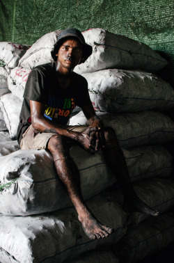 A young man takes a rest from packing coal in Yangon's harbour. He says he works barefoot most days. Yangon, Myanmar. March 2013.[Credit: Jeff McAllister]