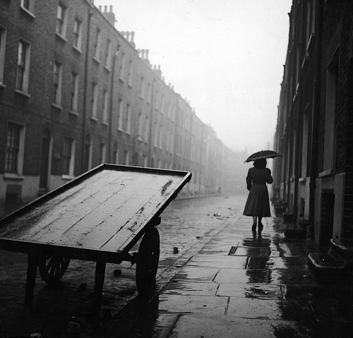 John Chillingworth A woman walks down a rainy street in post-war Whitechapel, 1952 From Picture Post/Getty Images
