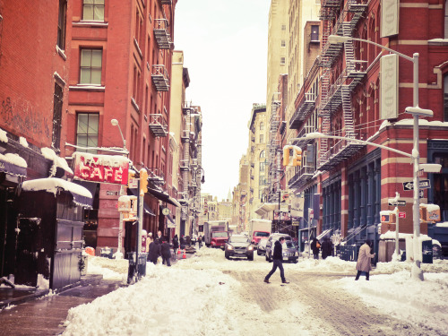 "New York City winter. Snow in Soho on Mercer Street.  Soho is so beautiful in the snow especially right after snow has freshly fallen and still sits like icing on the fire escapes and street signs.  This part of Soho is part of the Soho Cast Iron District which consists of 500 buildings that feature distinct cast-iron architecture spanning over a 26 block radius. Many of the buildings date back to the 1870s when the area was primarily residential. However, most of the residences during the later part of the 20th century were converted for commercial use which allowed Soho to play an integral role in the commercial development of New York City.  This is a view looking north up Mercer Street in Soho towards midtown. The Chrysler Building can be seen in the distance. The snow-covered sign on the left belongs to Fanelli's Cafe which has stood in this spot since the 1850s.  —-  This was taken during one of the last huge snowstorms we had in New York City back during the winter season of 2010-2011 with my Panasonic FZ-35 (loved that camera!). I have been pining away wishing for snow like this since we really haven't gotten snow in a major way here in NYC since that winter season. Photos like this one will just have to suffice, I guess :)   —-  View this photo larger and on black on my Google Plus page —-  Buy ""New York Winter - Snow in Soho"" Posters and Prints here, email me, or ask for help."