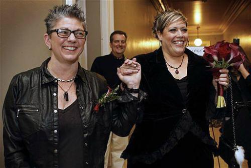 "Same-sex marriage now legal in Maine: ""Donna Galluzzo, left, and Lisa Gorney leave the City Clerk's office after obtaining their marriage license, early Saturday at City Hall in Portland, Maine. Same-sex couples in Maine are now legally permitted to marry under a new law that went into effect at 12:01 a.m. on Saturday."" (photo by Robert F. Bukaty/Associated Press)"