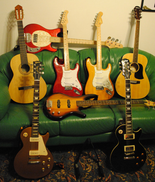 "Just Hanging Around. ""Here are the 8 gems in the crown of my gear obsession. Lying horizontally on the head of the couch: Stagg MB300 bass. Lying horizontally on the cushions: Ibanez GSR 180 Bass. Top row left to right: Yamaha C30M, Rooster Stratocaster (boutique guitar), Ink Music Stratocaster (hand-made in Nice, France), Arianna AR-15 acoustic.Bottom row left to right: Gibson Les Paul 60s Tribute, and Epiphone Les Paul Standard. Hope you enjoy gazing at them as much as I enjoy playing them!"" - Ivan Struk"