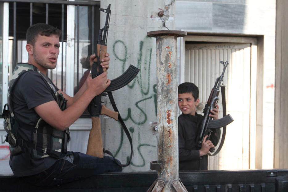 A Free Syrian Army fighter and a boy hold up weapons on a street at the Syrian town of Tel Abyad, near the border with Turkey, April 23, 2013. REUTERS/Hamid Khatib