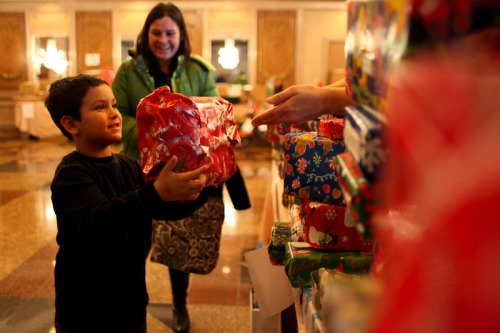 Jose Criespo, 10, receiving a gift from the relief group Secret Sandy at a holiday party on December 23, 2012. (photo: Stephen Nessen) Contd.