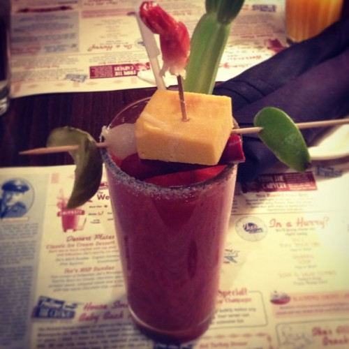 neil-gaiman:  areasofmyexpertise:  My Bloody Mary at Ike's came with celery, olive, cocktail onion, pickle, a block of cheese, a summer sausage, and a shrimp I mostly ate before I took this picture. I opted out of the garnish hoagie, side steak, and wheel of Stilton. (at Ike's Food & Cocktails)  Ike's at Minneapolis St Paul airport is a real restaurant. Here, in another photograph by Mr Hodgman, you see me reacting to the supergarnished Bloody Mary in question: