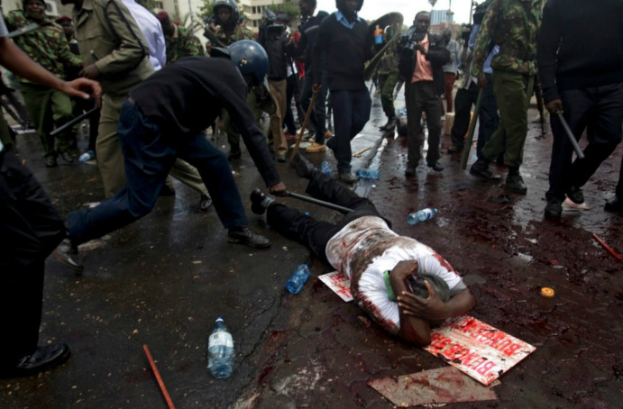 simply-war:  In Nairobi, Kenya, a demonstrator was beaten during a protest of corruption in Parliament. May 14, 2013. Daniel Inungu.