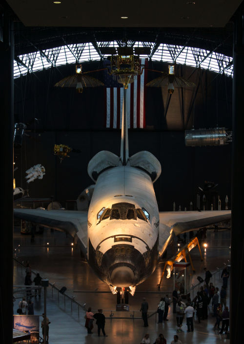 The space shuttle Discovery (OV-103) at the Smithsonian's Udvar-Hazy Center in Virginia. Discovery was the longest-serving shuttle and participated in high-profile missions such as the deployment (and repair) of the Hubble Space Telescope, the last docking mission to the Russian Mir space station, and the first shuttle docking mission with the International Space Station. With 39 missions flown between 1984 and 2011, Discovery has spent a full year's worth of time in space.  In April 2012, Discovery arrived in Virginia to replace the Enterprise (OV-101) at the Udvar-Hazy Center. The Enterprise is now aboard the USS Intrepid as a new addition to the Intrepid Sea, Air & Space Museum in New York.