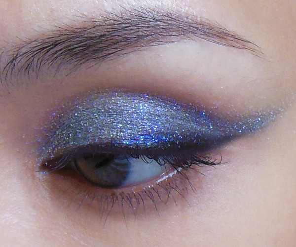 makeupbox:  Grey with a Lavender Twist: Duochrome Sparkle Eyeshadow Tutorial — Because Maybelline's Color Tattoo shadows were SUCH a great product to use as glitter base, I couldn't resist doing a second version in a slightly winged out kitten-eye shape. This time, I used a grey base (Audacious Asphalt) and a crystalline white glitter with a violet sheen on top. The image above was taken in daylight, as I had a lot of trouble capturing the true color of the glitter (Virgo by Lime Crime) in flash photographs. It kept showing up white in the camera, although it's a violet in real life. (Scroll to bottom of post for another image showing the duochrome effect). You will need: Black pencil Grey cream shadow or base Pale white glitter with lavender sparkle (you can actually use any pale glitter; it doesn't need to be a white with violet duochrome, but if you can get hold of some, it adds a twist to the look)  —  Step 1: First, I did a simple black liner swatch along the upper lid. Do it in a rough triangle so it's thick at the outer corners. —  Step 2: Here's the fun step. You apply the grey shadow using a synthetic concealer brush, and you want to line it up exactly above the black liner you did earlier (overlapping a tiny bit is fine) and then drag it out past the outer corners of the eye.  This actually scrapes the black and pulls it out into a nice sharp wing. The grey should go up to the hollow of the socket line, so continue to apply if that stroke with the brush did not cover everything. —  Step 3: The simple part is the glitter. Just quickly use the same brush to press a thin layer of pale white/violet glitter over the grey cream shadow. — Step 4: Finish with black mascara. Because the glitter doesn't really go down to the base of the lash line, you can easily wear half-strip lashes with this look for some extra drama. It's quite a neutral look but there's just that bit of extra sparkle in a different color when your eyes catch the light.  To show you how the duochrome looks, I have an image taken in shaded interior lighting (daylight) as well. Grey, but not grey!