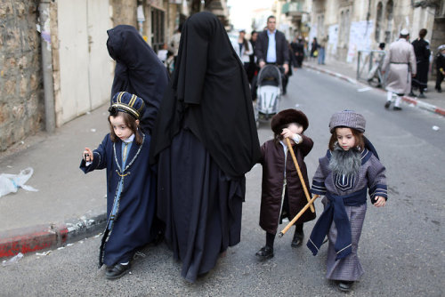 mohandasgandhi:   An ultra-Orthodox Jewish women belonging to the religious sect 'Women of Lease' with their children in Mea Shearim neighborhood of Jerusalem, Israel, 25 February 2013, during celebrations of the joyous holiday of Purim. Purim is a celebration of the Jews' salvation from genocide in ancient Persia, as recounted in the Book of Esther, and many religious Jews drink openly during the holiday. (Credit: EPA)  Kid over my shoulder: What are you looking at? Muslims dress so weird, wow.  lo don't we have to go in and liberate these women?