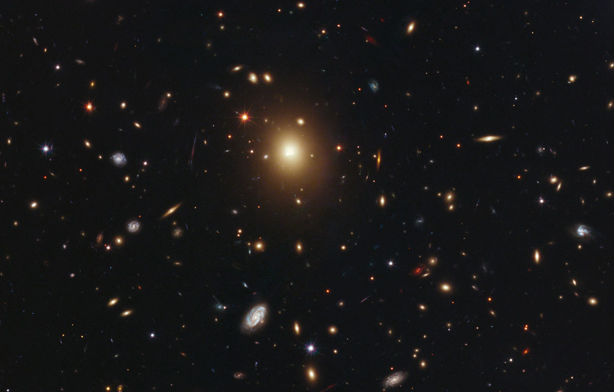 Day 15 of the 2012 Hubble Space Telescope Advent Calendar, one of 25 photos (eventually). The giant elliptical galaxy in the center of this image is the most massive and brightest member of the galaxy cluster Abell 2261. Spanning a little more than one million light-years, the galaxy is about 10 times the diameter of our Milky Way galaxy. The bloated galaxy is a member of an unusual class of galaxies with a diffuse core filled with a fog of starlight. Normally, astronomers would expect to see a concentrated peak of light around a central black hole. The Hubble observations revealed that the galaxy's puffy core, measuring about 10,000 light-years, is the largest yet seen. The observations present a mystery, and studies of this galaxy may provide insight into how black hole behavior may shape the cores of galaxies. The immense gravity of the galaxy warps the light passing by, smearing out the images of background galaxies, as seen by Hubble. (NASA, ESA, M. Postman (STScI), T. Lauer (NOAO), and the CLASH team)