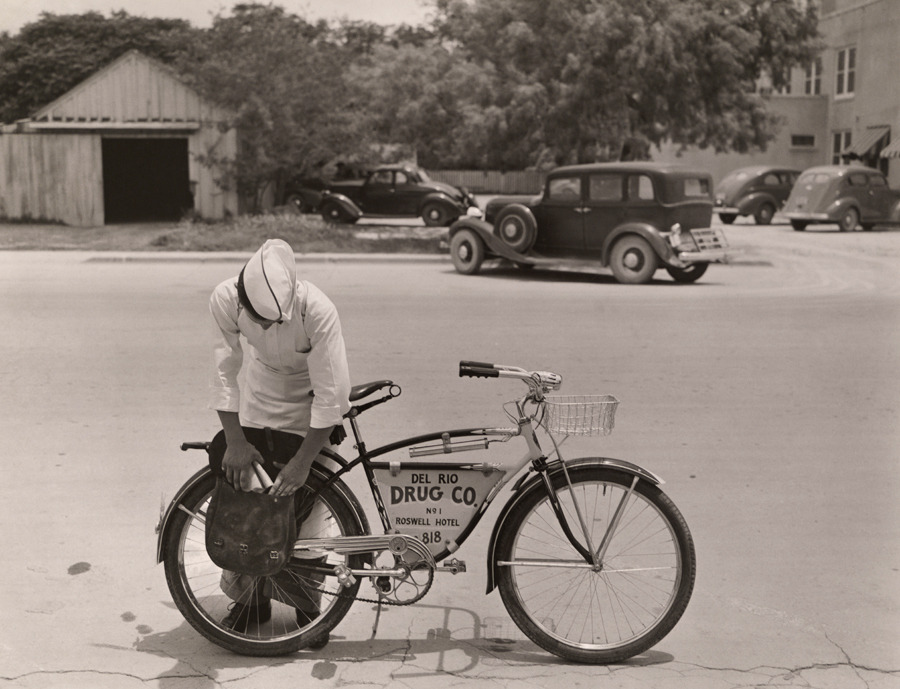 "A ""drugstore cowboy"" preparing to deliver orders on his bicycle in Texas, 1938.Photograph by Luis Marden, National Geographic"