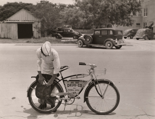 "natgeofound:  A ""drugstore cowboy"" preparing to deliver orders on his bicycle in Texas, 1938.Photograph by Luis Marden, National Geographic"
