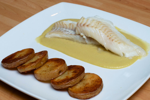 Tonight's dinner: haddock with leek and potato sauce and sautéed potatoes, from Heston Blumenthal At Home  My first chance to use both birthday gifts I received from my sister Hayley: a Kenwood hand blender (which I used to make the sauce) and a copy of Heston Blumenthal At Home (from which I took the recipe).  Turned out pretty good. Perhaps a little elaborate for a weeknight meal — the recipe (with some minor alterations) can be seen here if you're curious. Wasn't my prettiest plate of food; the fish had been manhandled by the fish counter staff in Morrisons so wasn't holding together very well, unfortunately. I'm pleased with the composition of the plate, though. I've been putting a lot more work into how I present my food lately, and although I still have a long way to go, I feel like I'm at least making progress.