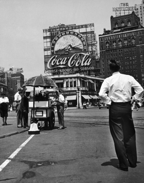 bygoneamericana:   A large Coca Cola sign and thermometer registers 100 degrees on top of building next to the Mayflower Hotel in Columbus Circle during a heat wave. New York, 1944. By Marie Hansen