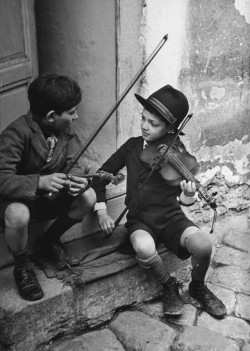 Gypsy children play violin in the streets.Hungary, 1939.