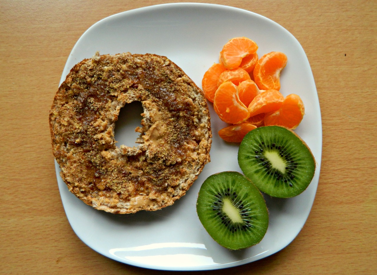 Half a wholewheat bagel with natural peanut butter, ground flaxseed and agave, a tangerine and a kiwi.