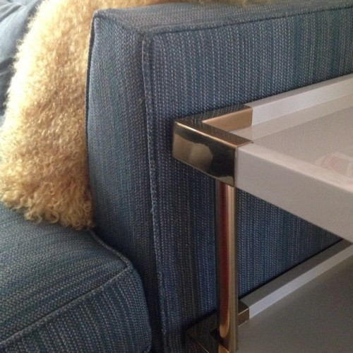 Decorative #details at a client's house. #brass corners and legs of a #lacquered table against a #blue studio #sofa and #yellow toss cushion. #interiors #design #decoration #custom #home #halifax