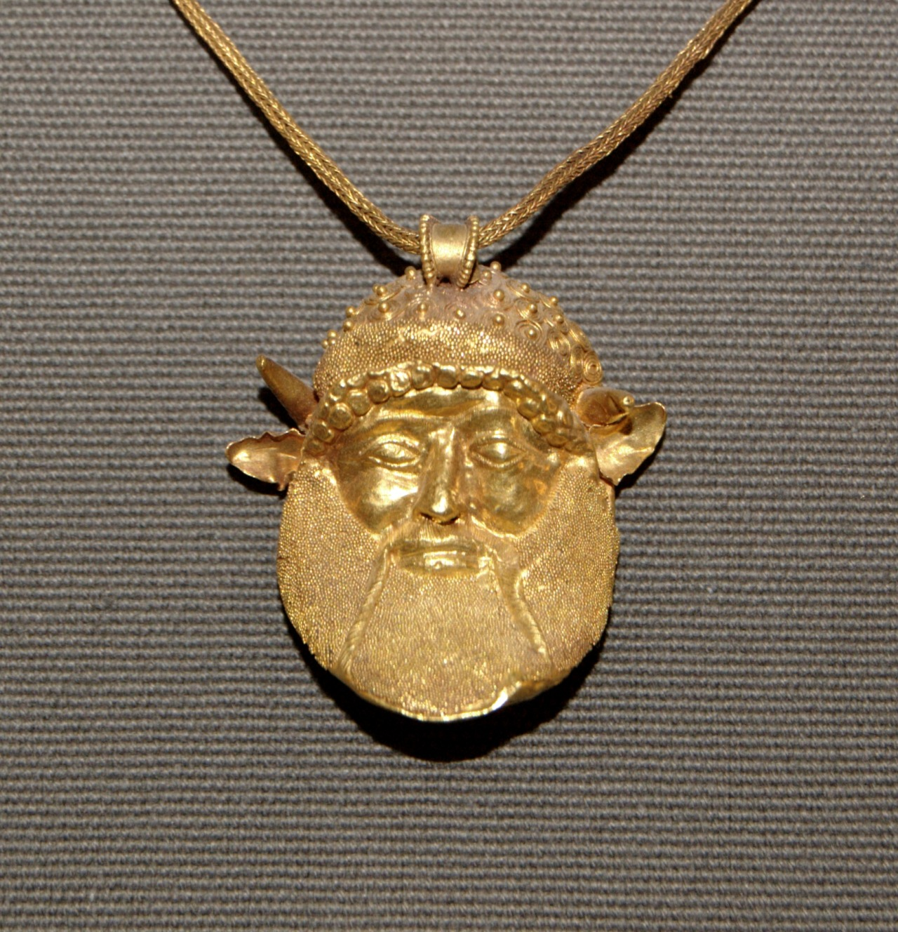Pendant with the head of the river god Achelous, Etruscan. Courtesy & currently located at the Louvre, France:  This gold necklace, from the early 5th century BC, is a splendid example of the imaginative decoration and virtuoso techniques used by Etruscan goldsmiths of the Archaic period. The repoussé pendant, with details in graining and filigree, represents the river god Achelous, identified by his extensive beard and bull-like horns. His image was thought to have protective powers. A masterpiece of the Campana collection, the pendant inspired a number of 19th-century copies.  Photo taken by Bibi Saint-Pol