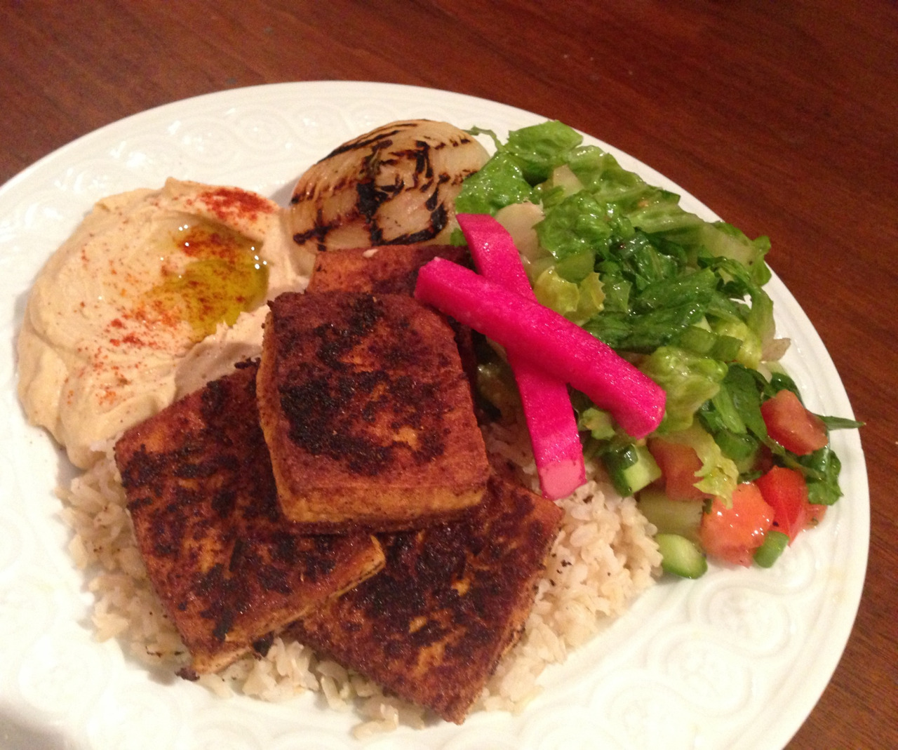 Moroccan spiced fried tofu, brown basmati rice, hummus, grilled onion, fatoush salad, and pickled turnip.