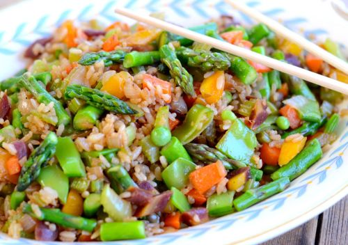 Delicious Veggie Fried Rice This is a delicious way to use leftover rice, yum! It's easy to make, just chop up whatever vegetables you have on hand. I start with chopped onions in a hot skillet with a little coconut oil, chop and add the densest vegetables first. I used a bunch of fresh veggies from my spring garden including shallots, rainbow carrots, peas, and cilantro. I also used store bought sweet onion, garlic and asparagus. Season with 1 tblsp organic soy sauce, a little sesame oil, and some Chinese Five Spice, a little red chili flake or cayenne, and coriander powder. Add the rice along with a little stock once the veggies are most of the way cooked. Yum!
