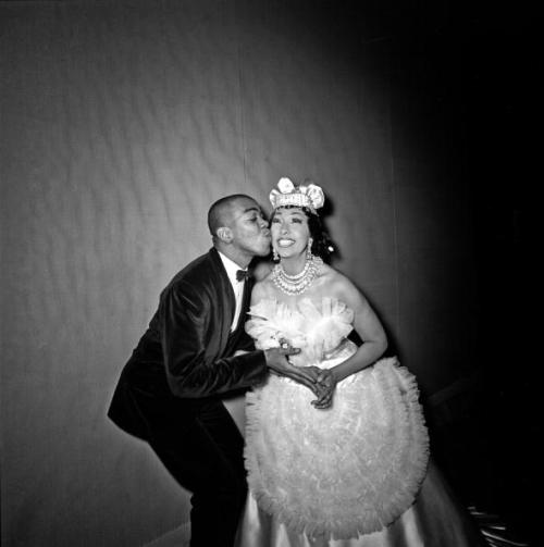 "Josephine Baker getting a little kiss from Geoffrey Holder in 1964. I'm guessing this is probably backstage at ""Josephine Baker And Her Company,"" her musical revue that appreared briefly on Broadway that year. Both Mr. Holder and his wife Carmen de Lavallade performed in the show with Ms. Baker and, in the video clip linked in the comment section, Mr. Holder discusses, with his signature verve, what a delight it was for he and Ms. de Lavallade to work with Ms. Baker. Photo: Michael Ochs Archives."