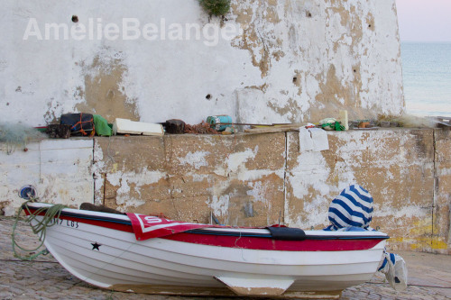 Boat, Burgau, Portugal This picture was taken in Burgau, Portugal. This image blends texture and vibrant colors. I like all the cracks in the wall behind the boat mixing with the blues, reds and greens. I also enjoy the difference between the busy foreground and the calmness of the ocean in the background.
