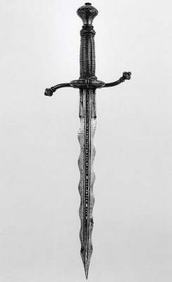 "art-of-swords:  Parrying Dagger (pugnale bolognese) Dated: 1550–75 Culture: Italian Medium: partly gilt steel, brass, and wood Measurements: wt. 15 oz. (425 g) Designed to be used together with a rapier, this dagger is fitted with a side ring, recurved quillons, and a depression at the base of one side of the blade to accommodate the thumb and facilitate a firmer grip. The waves in the blade may be intended to act like ""speed bumps"" in breaking the impact of a blow from an opponent's blade. The piercing of the fullers (grooves) is a decorative motif.  Source: © 2000–2012 The Metropolitan Museum of Art"