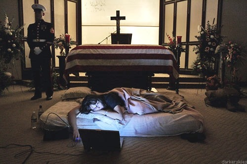 "In the photo here, the night before the burial of her husband 2nd Lt. James Cathey of the United States Marine Corps, killed in Iraq, Katherine Cathey refused to leave the casket, asking to sleep next to his body for the last time. The Marines made a bed for her, tucking in the sheets below the flag. Before she fell asleep, she opened her laptop computer and played songs that reminded her of ""Cat."" The Marines, per her request, stood guard the entire time she slept there along side her fallen hero. Katherine says that she thinks that her husband would have wanted it that way."